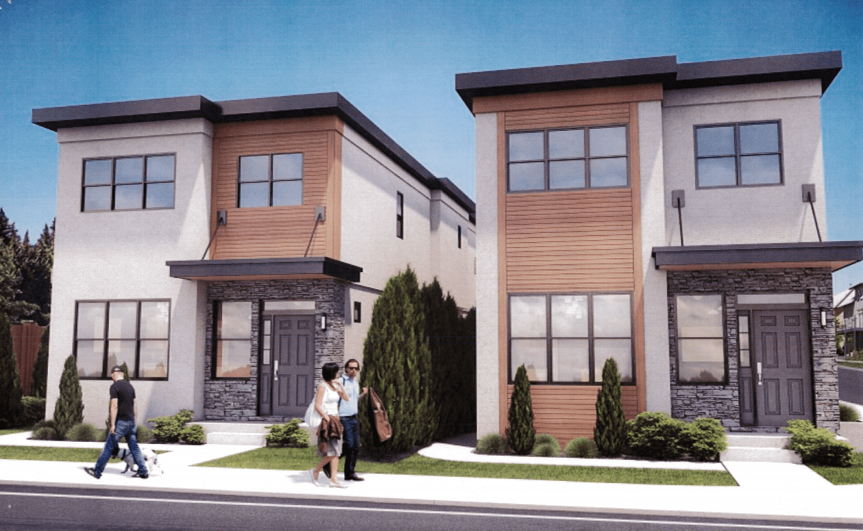 Photograph of several multi-story townhomes along a street.